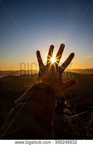 Sunset Sun Rays View Through The Fingers Of A Feminine Open Hand
