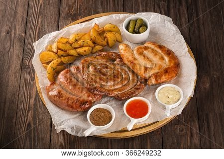 Assorted Grilled Sausages On A Wooden Board. Served With Potato Wedges, Three Kinds Of Sauce And Pic