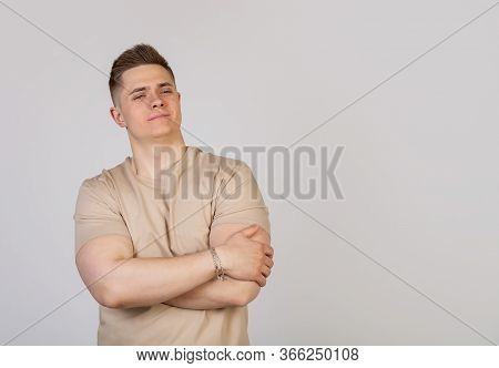 Handsome Young Man Crossed His Arms Over His Chest With An Average Expression On His Face. Confident