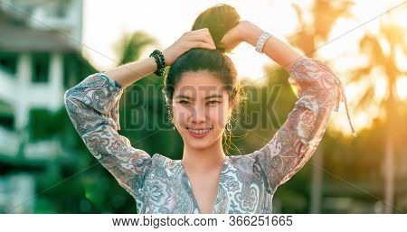 Woman Portrait With Hard Sunflare On With Beach Resort On The Background For Summer Beach Relaxation