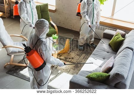 Coronavirus Pandemic. A Disinfectors In A Protective Suit And Mask Sprays Disinfectants In House Or