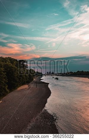 Shore-side Of River Thames At Sunset With Orange Rays From The Sun Reflecting Off The River. Travel,