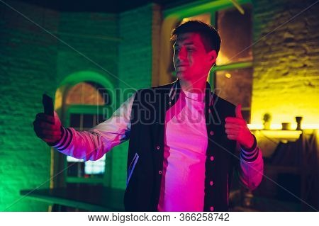 Selfie. Cinematic Portrait Of Stylish Man In Neon Lighted Interior. Toned Like Cinema Effects, Brigh