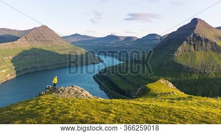 Lonely tourist in yellow jacket looking over majestic fjords of Funningur, Eysturoy island, Faroe Islands. Landscape photography