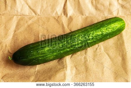 Big Cucumber With Water Drops On Peper Crumpled Background. Top View