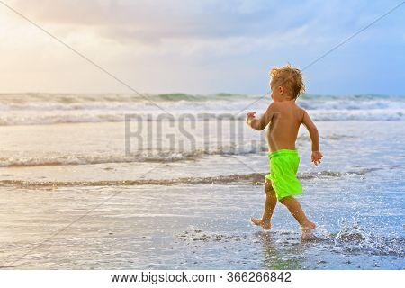 Happy Family Have Fun On Tropical Sea Beach Resort. Funny Baby Boy Run With Splashes By Water Pool A