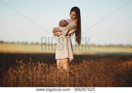 Happy Child And His Mom Have Fun Outdoors In A Field. Mom Holds The Child In Her Arms, And The Child
