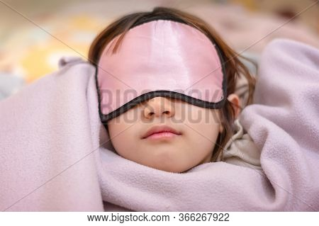 Young Girl Naps With An Eye Patch And A Cozy Blanket