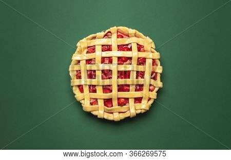 Strawberries And Rhubarb Pie With A Lattice Crust, Above View On A Green Background. Top View With A