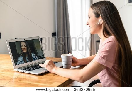 Distance Communication With Friends Via Video Call. A Young Attractive Woman Talking Via Video With