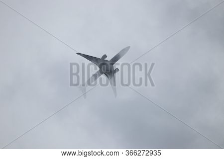Airplane Flying In The Sky, View Through The Storm Clouds. Silhouette Of A Commercial Plane During T