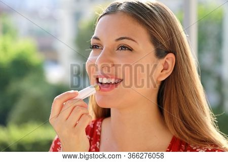 Smiling Young Woman Applying Sun Protection On Her Lip Outdoor
