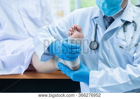 Close-up Hand Wear Medical Gloves Doctor Examines The Leg Of The Woman's Heel For Heel Spurs, Pain I