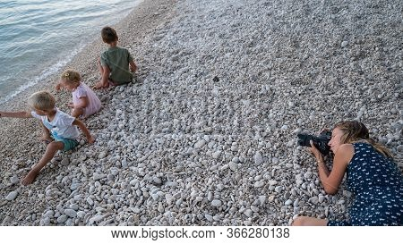 Young Mother Lying On Pebble Beach In The Evening To Take Photos Of Her Three Children Playing With