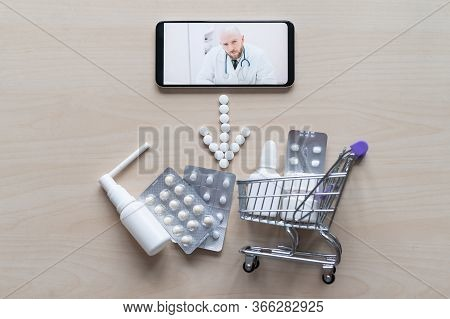 A Male Pharmacist Recommends Buying Medicines. Top View On The Smartphone Arrows Laid Out Of Tablets