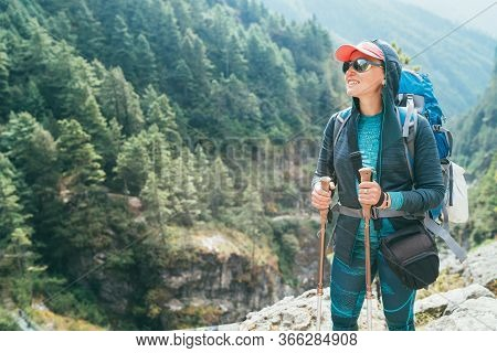 Young Smiling Female Photographer Walking Everest Base Camp Route At Canyon Near Suspension Hillary