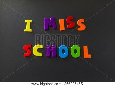 The words I miss school written on a refrigerator door with magnet letters. Message during self isolation from COVID-19 corona virus flu