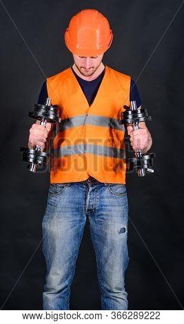 Man In Helmet, Hard Hat Holds Heavy Dumbbells, Black Background. Worker, Contractor, Builder On Busy
