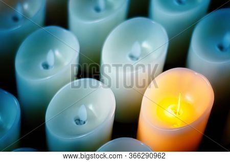 Odd One Out. One Lit Candle Between The Extuingished Ones