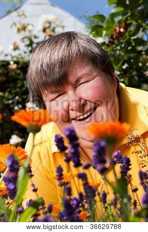 mentally disabled woman is in the garden and smell of flowers poster
