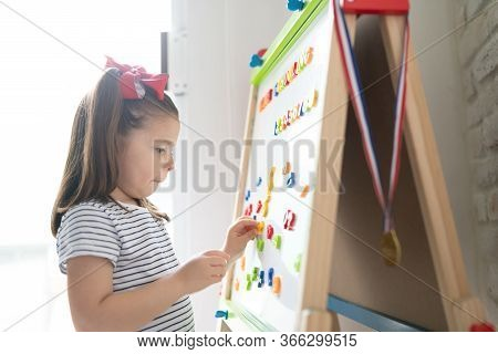 Profile View Of A Cute Little Girl Using A Magnet Board To Learn Letters And Numbers At Home