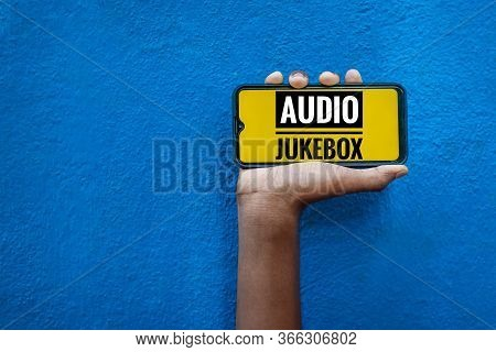 Audio Jukebox Word On Smart Phone Screen Isolated On Blue Background With Copy Space For Text. Perso