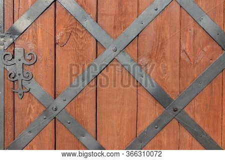 Close-up Of A Wooden Door With Wrought Iron Lattice