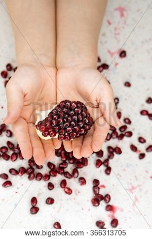 Child Holding And Showing In His Hands Pomegranate, White Table Background. Pomegranate Fruits Are R
