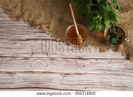 Herbal Tea From Nettle Dioecious With Honey On Sacking On A Wooden Background. Alternative Medicine,