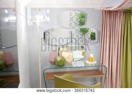 Three Mirrors Hang On The Wall By The Bedside Table. On The Table Are Decorative Elements, Vases. On