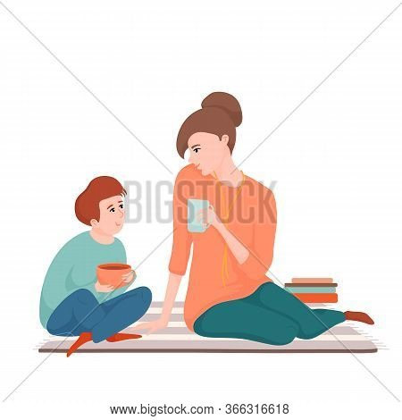 Young Beautiful Mother And Teenage Son Sitting On The Carpet, Drinking Tea And Talking, Spending Tim