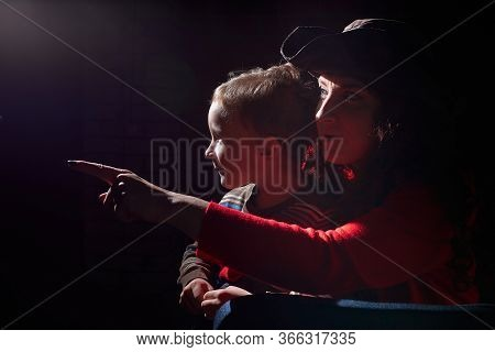 Ugle Oman In Red Sweater And Pirate Hat With Curly Hair Posing With Small Boy On Black Background. A