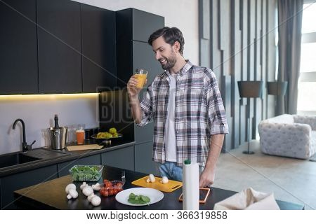 Smiling Man With Glass Of Juice Standing Near The Table.