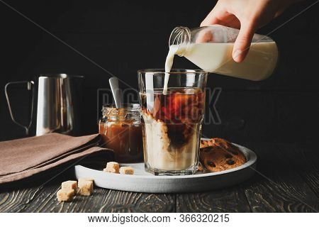 Woman Pours A Milk In Glass Of Coffee. Composition With Ice Coffee