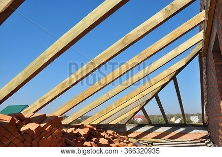A Close-up On Framing The Rooftop Of A Brick House With Trusses, Roof Beams, Roof Eaves, Braces And