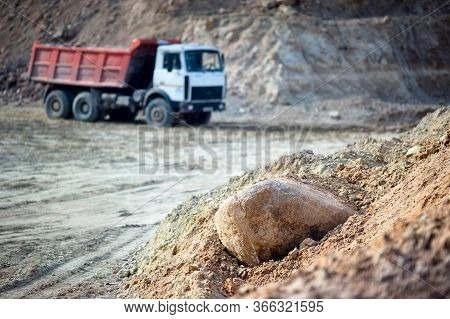 Pile Of Ore Rocks Over Out Of Focus Background With Heavy Multi-ton Mining Truck Exporting Minerals