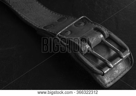 Old Leather Belt With A Double Metal Buckle. Close-up Of A Wide Dirty Belt Or Collar On A Dark Table