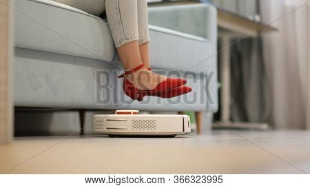 Robotic Vacuum Cleaner Cleaning The Room While Woman Resting On Sofa.