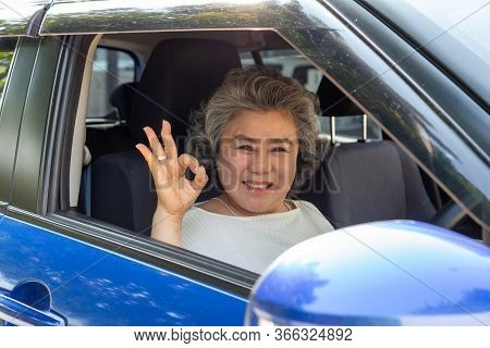 Asian Senior Woman Driving A Car Showing Ok With Glad Positive Expression During The Drive To Travel