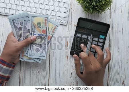 Young Man Are Calculating On Calculator Investment Costs