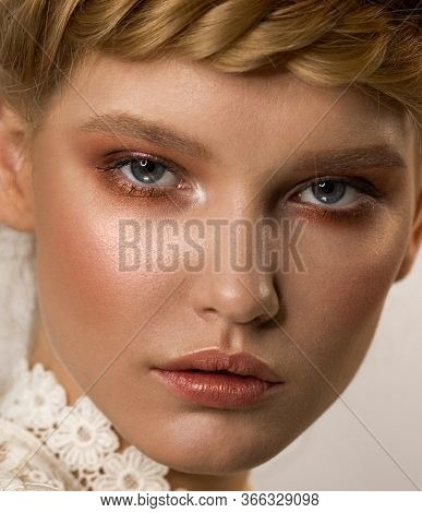 Close-up Face Of A Woman With Stylish Makeup. Shades Of Bronze In The Eyes. Beige Lipstick With A Go