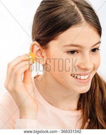 Individual Earplugs For Children. Girl Holding Individual Ear Plugs Near Ear, Closeup