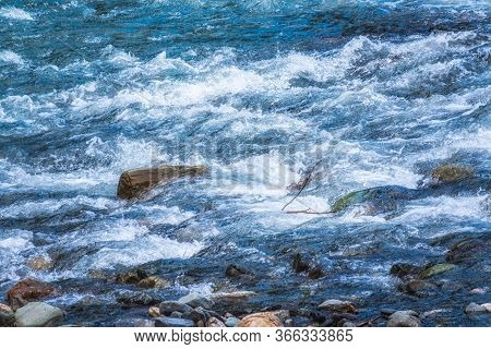 Stones In Water Riffle Of Mountain River. Powerful Water Stream Among Stones In Mountain Creek With