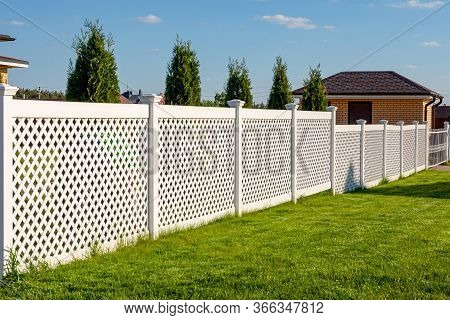 White Vinyl Fence In A Cottage Village. Several Panels Are Connected By Columns. Fencing Of Private