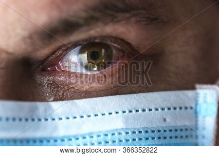 Tears In Eyes Of Crying Male Doctor  In  Mask.  Face Close-up. Pandemic And Virus Epidemic. Coronavi