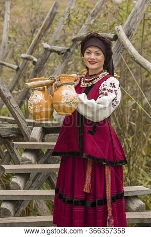 A Woman In Traditional Clothes Carries Water In Old Barrels. Old Jugs Are Carried By A Girl In A Sty