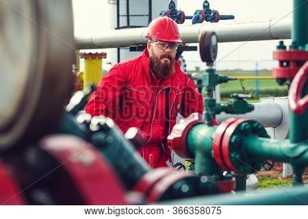 Engineer In Hard-hat. Face Behind Pipeline Machinery, Fuel And Oil Refinery.