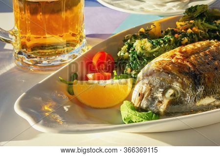 Balkan Cuisine. Sunday Lunch: Mug Of Beer And Grilled Fish With Green Vegetables And Slice Of Lemon