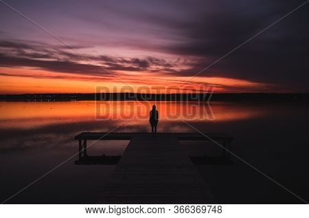 Silhouette Of A Man Standing On A Wooden Pier In The Lake Against The Background Of An Incredible Co