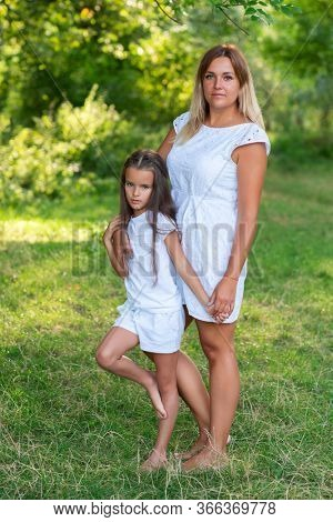 Little girl hugs her mother in summer forest nature outdoor. Portrait of mom and daughter wearing white clothes. Family walks barefooted in park. Trust, kindness, maternity, parenthood, confidence